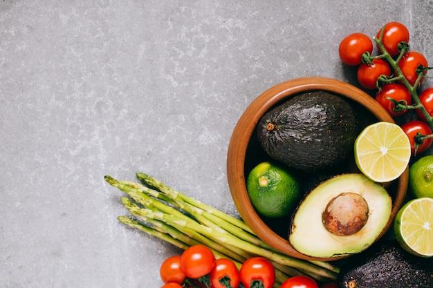 Légumes frais et sains dans une assiette en bois sur fond gris