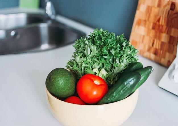 Légumes frais de saison concombres, tomates, légumes verts dans les plats sur la table de la cuisine à la maison