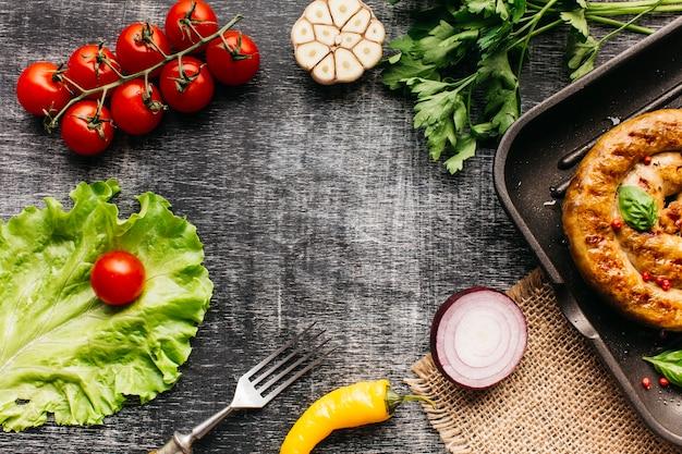 Légumes frais et saucisses d'escargot grillées disposées dans un cadre circulaire