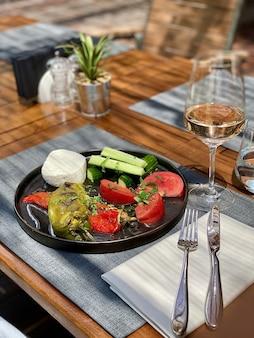 Légumes frais servis dans une assiette noire, avec une fourchette, un couteau et un verre de vin rosé