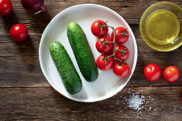 Légumes frais, tomates et concombres sur une table rustique