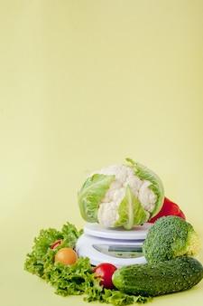 Légumes frais sur vase sur fond jaune. alimentation saine, planification de l'alimentation, perte de poids, désintoxication, concept d'agriculture biologique.