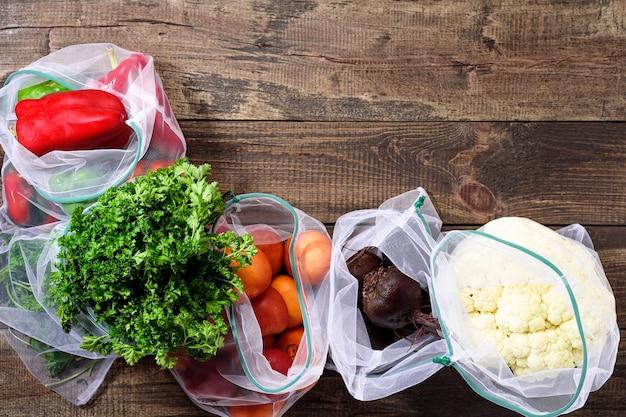 Légumes frais et verts dans des sachets écologiques réutilisables sur fond brun en bois avec espace copie