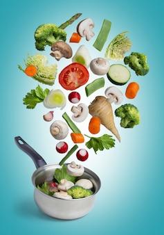 Légumes frais voler dans un pot, isolé sur bleu