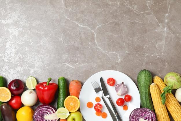Légumes, fruits, assiette et couverts sur gris