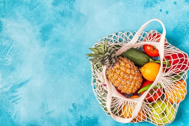Légumes et fruits frais en filet de sac, vue de dessus.