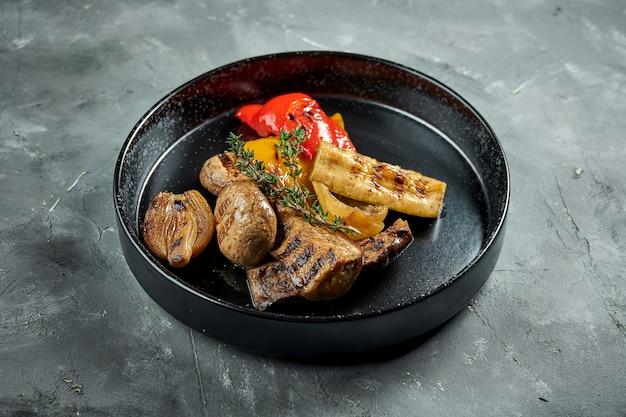 Légumes grillés appétissants servis dans une assiette noire sur une surface grise