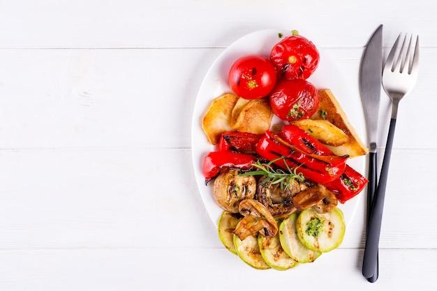 Légumes grillés sur une assiette en bois blanc