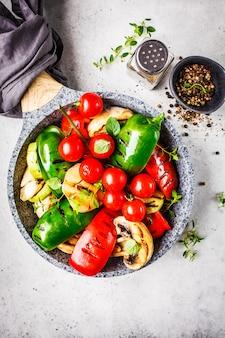 Légumes grillés (poivrons, courgettes, champignons et tomates en casserole, fond blanc.