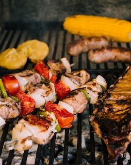 Légumes grillés et saucisses sur du charbon de bois chaud