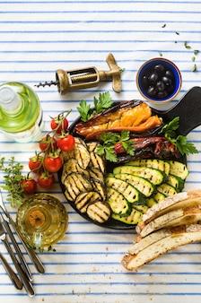 Légumes grillés sur la table avec du vin blanc, du pain frais et des herbes aromatiques. menu d'été