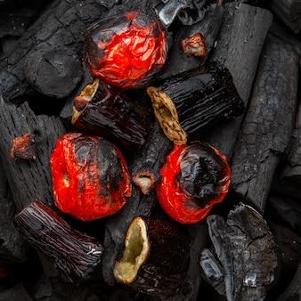 Légumes grillés de tomates et d'aubergines sur charbon de bois, à plat.
