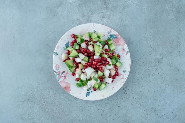 Légumes hachés et salade de fruits dans un plat.