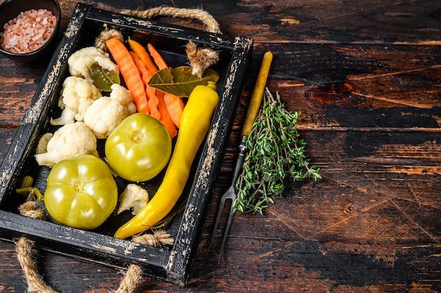 Les légumes marinés et cornichons faits maison se conservent sur un plateau en bois sur une table en bois. vue de dessus.