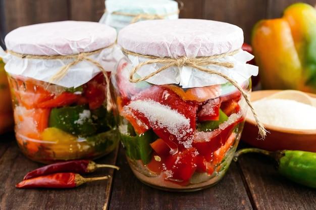 Légumes marinés dans un pot de verre: piments rouges et verts chauds avec du sucre. fermer.