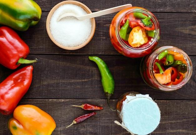 Légumes marinés dans un pot de verre: piments rouges et verts chauds avec du sucre. vue de dessus