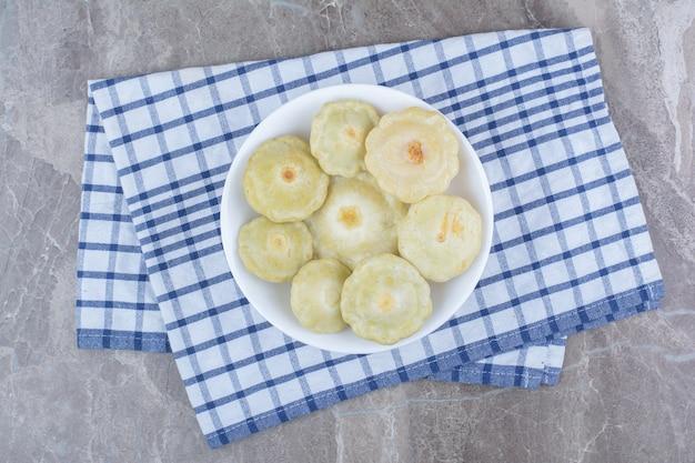 Légumes marinés maison dans un bol blanc.