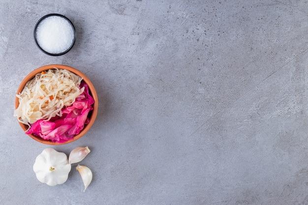 Légumes marinés mélangés placés sur une table en pierre.