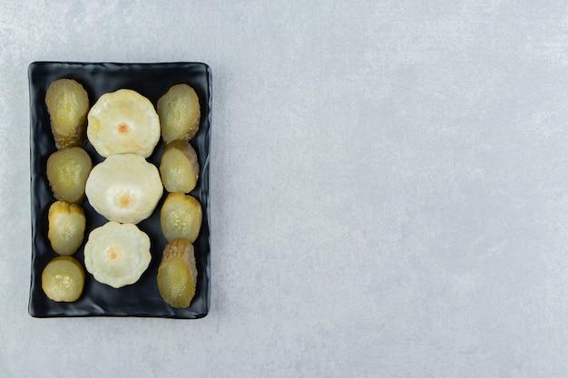 Légumes marinés tranchés sur plaque noire.
