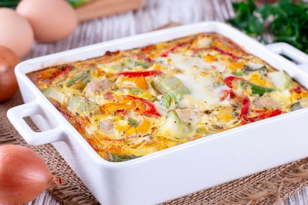 Légumes mélangés cuits au four avec des boulettes de viande sur fond de bois
