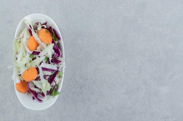 Légumes mélangés dans un bol , sur le fond de marbre.