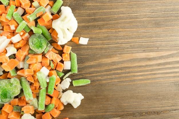 Légumes mélangés surgelés sur table en bois. carotte crue hachée, chou-fleur, oignon, haricots verts et choux de bruxelles