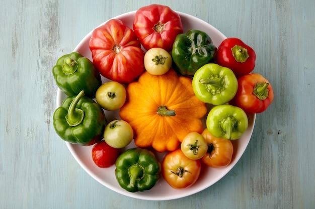 Les légumes mûrs du jardin sont disposés sur une assiette blanche. récolte