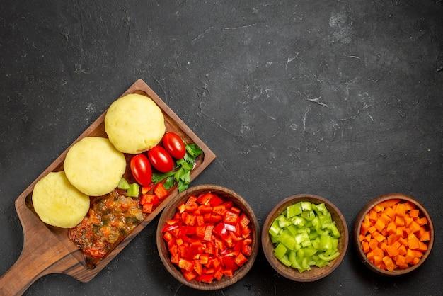 Légumes non cuits sur une planche à découper brune