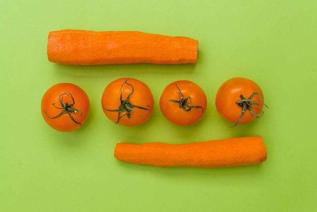 Légumes orange sur un fond vert coloré, couper les carottes et les tomates,