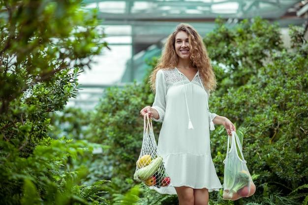 Légumes oraniques. femme en robe blanche portant des sacs avec des légumes et se sentir bien