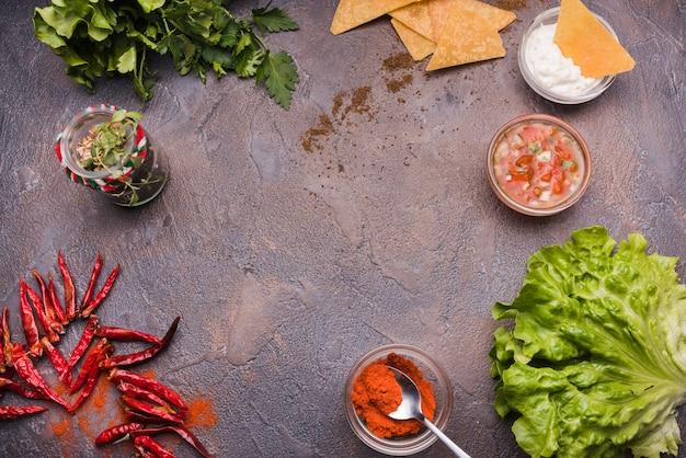 Légumes parmi les nachos avec sauce et piment
