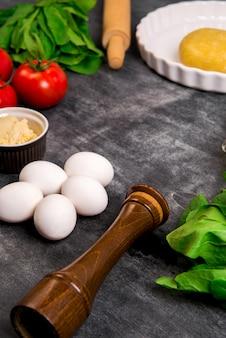 Légumes et pâte sur une surface en bois grise