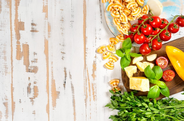 Légumes et pâtes vu d'en haut sur une table en bois blanc