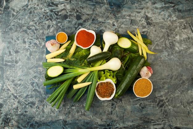 Légumes sur planche en bois sur une pierre. young herbs oignons ail graines vertes jaune maïs zucchini écluses éclairantes ment sur un panneau de bois foncé sur un texturé.