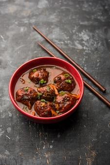Légumes ou poulet mandchourie avec sauce - nourriture populaire de l'inde servie dans un bol avec des baguettes