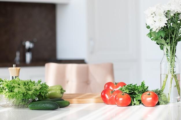 Légumes pour salade verte fraîche et saine sur table cuisine ensoleillée blanche pour la cuisine maison