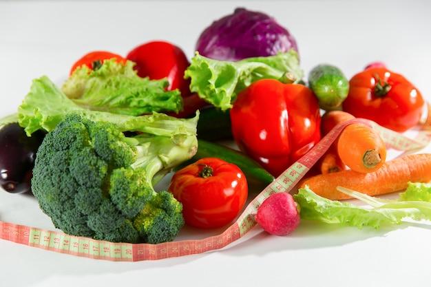 Légumes et ruban à mesurer, nature morte isolé sur fond blanc.