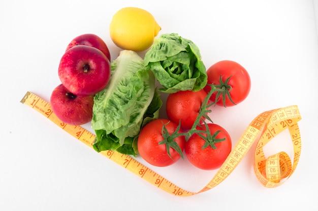Légumes avec ruban à mesurer sur une table blanche