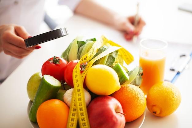 Légumes et ruban à mesurer sur tableau blanc.