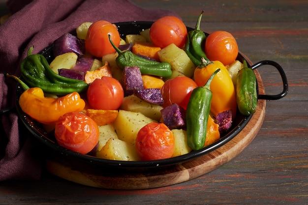 Légumes rustiques cuits au four dans un plat allant au four. repas végétarien de saison sur une table en bois sombre avec une serviette en lin.