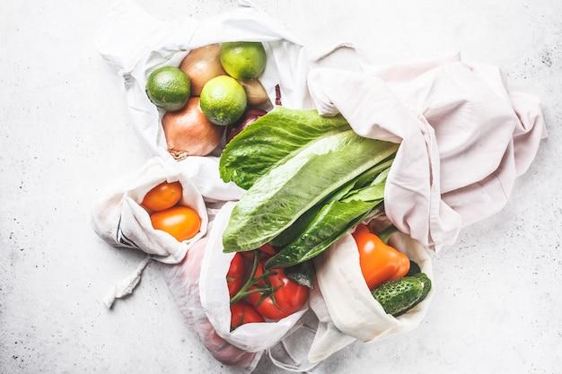 Légumes en sacs de coton écologique, poivron, tomate, laitue, concombre, citron vert, oignon. zéro gaspillage alimentaire.