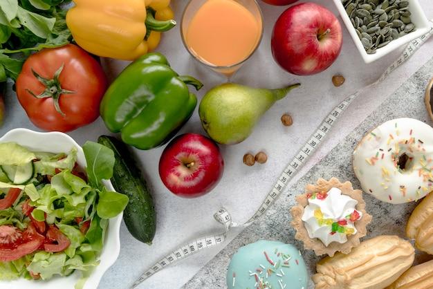 Légumes sains; jus; fruit; aliments sucrés; graines de citrouille et noisettes avec ruban à mesurer