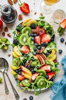 Légumes sains et salade de fruits à plat garnis de bleuets