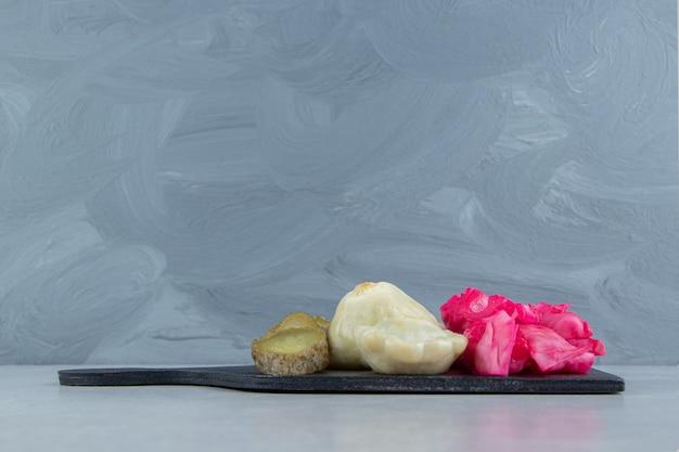 Légumes salés assortis sur tableau noir.