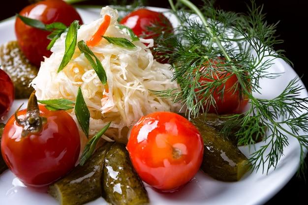 Légumes salés, marinés, tomates, concombres, choux, sur une plaque blanche