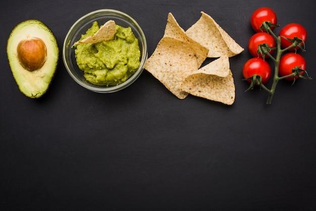 Légumes et sauce dans un bol près des nachos