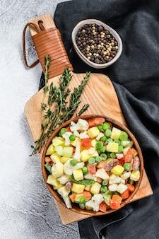 Légumes surgelés. brocoli, tomates cerises, maïs, pois, carotte. fond blanc. vue de dessus.