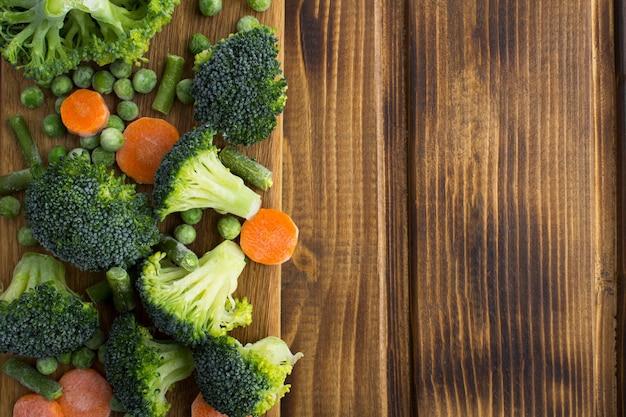 Légumes surgelés dans la planche à découper sur le bois brun