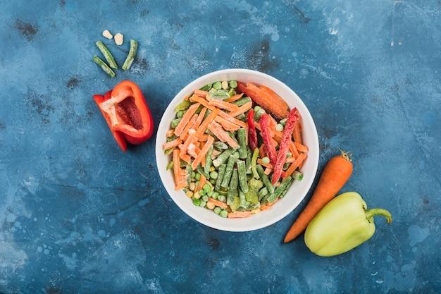 Légumes surgelés: mélange de légumes mexicains dans une grande assiette blanche sur fond bleu.