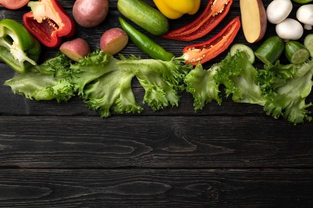 Légumes sur une table en bois noir, vue de dessus et avec copie espace au centre